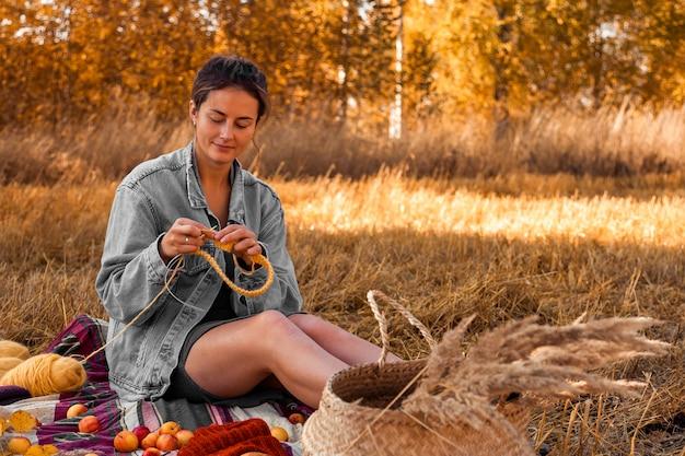 Eine junge frau in einer stilvollen kleidung, die gelben hut mit der nadel und natürlicher wolle, sitzend auf einem plaid mit einem picknickkorb, äpfel strickt konzept einer freiberuflerarbeit im freien