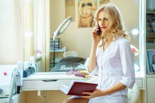Eine junge frau in einer weißen robe, die um das telefon im büro eines kosmetikers ersucht.