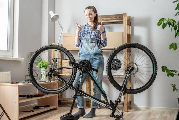 Eine junge frau in einer werkstatt neben einem fahrrad zeigt zwei daumen nach oben. konzept der wartung, befestigung und vorbereitung des fahrrads für die neue saison