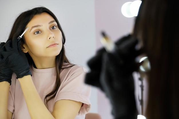Eine junge frau in handschuhen kämmt ihre augenbrauen in einem schönheitssalon