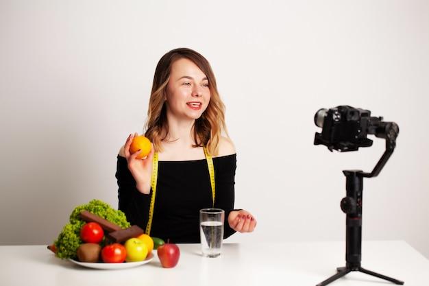 Eine junge frau in lightroom schreibt einen blog über gewichtsverlust und gesunde ernährung