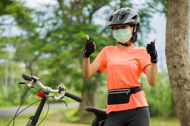 Eine junge frau in medizinischer maske fährt fahrrad