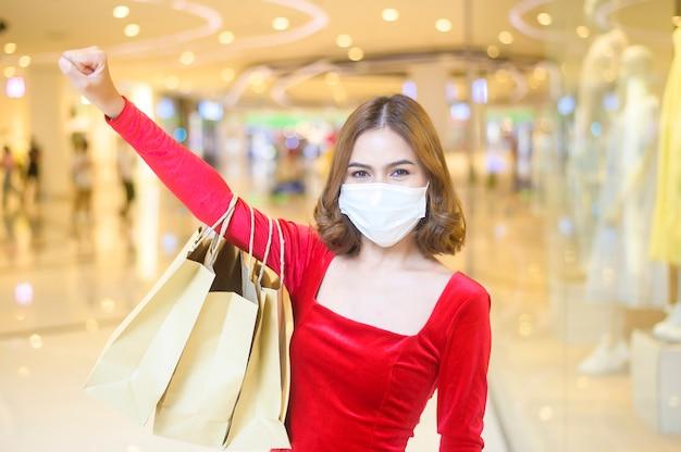 Eine junge frau in rotem kleid mit schutzmaske im einkaufszentrum, die nach dem covid-19-pandemiekonzept einkauft.