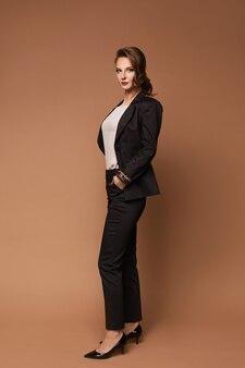 Eine junge frau in stilvollem anzug und weißer bluse posiert über der beigen oberfläche