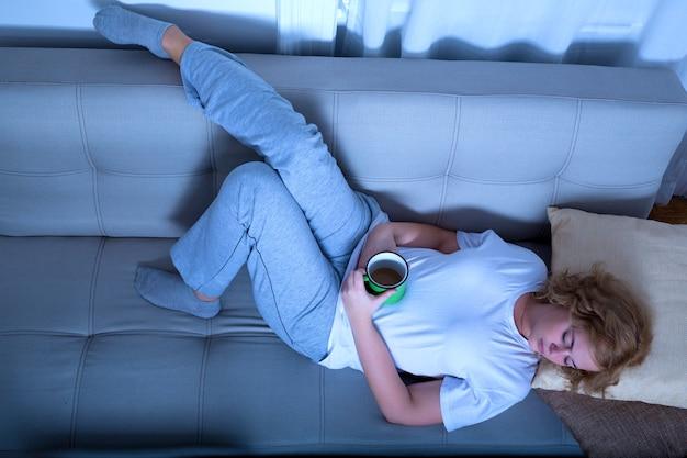 Eine junge frau in übergröße, die am frühen morgen eine tasse kaffee auf dem sofa hält.