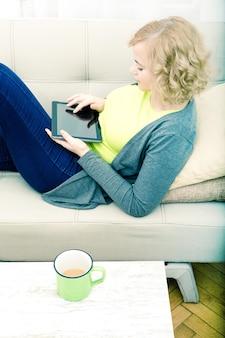 Eine junge frau in übergröße mit einem tablet pc, der auf einem sofa ruht.