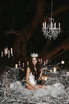 Eine junge frau in weißen satinwäsche und einer krone sitzt in einem riesigen nest mit einer kerzenlaterne in der hand