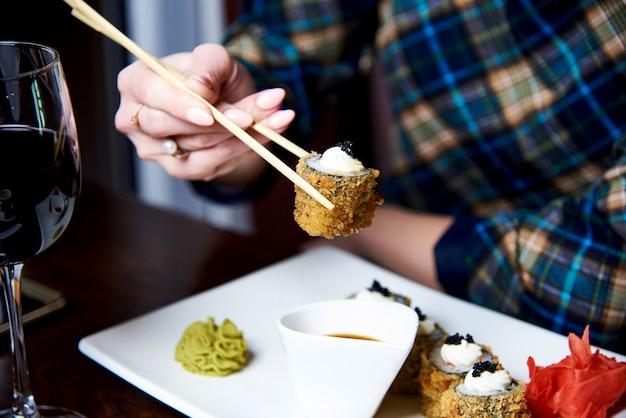 Eine junge frau isst in einem japanischen restaurant zu abend.