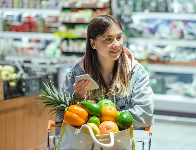 Eine junge frau kauft lebensmittel in einem supermarkt mit einem telefon in der hand.