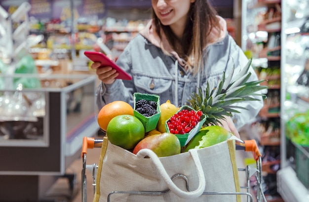 Eine junge frau kauft lebensmittel in einem supermarkt mit einem telefon in der hand