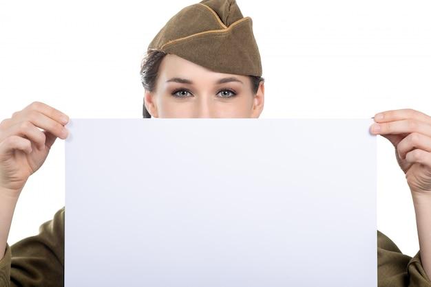 Eine junge frau kleidete im wwii militär uns die uniform an, die leeres leeres schild mit einem copyspace zeigt