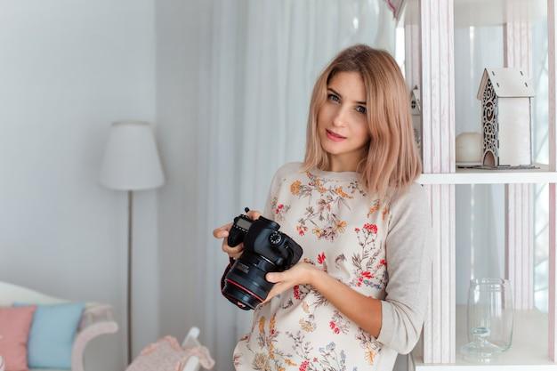 Eine junge frau lächelt mit einer kamera in den händen