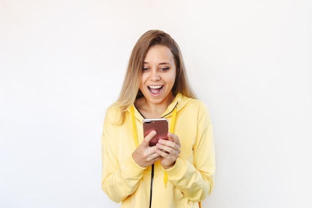 Eine junge frau lächelt und hält ein handy, das auf den bildschirm schaut das erstaunte mädchen benutzt smartphone