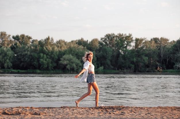 Eine junge frau läuft vor dem hintergrund des flusses eine schöne glückliche blondine in einem weißen top und...