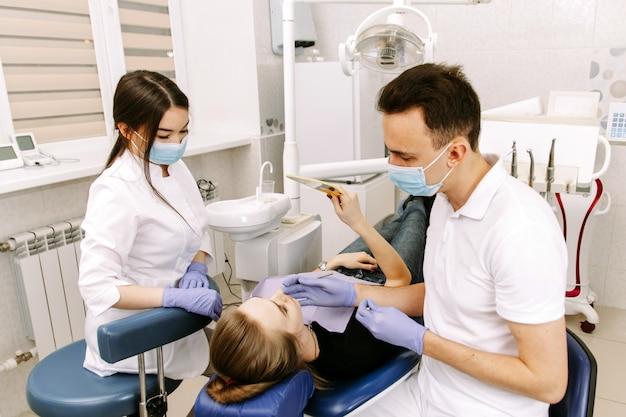 Eine junge frau liegt auf dem zahnarztstuhl
