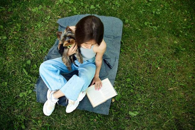 Eine junge frau liest ein buch in der natur neben dem kleinen hund yorshir terrier