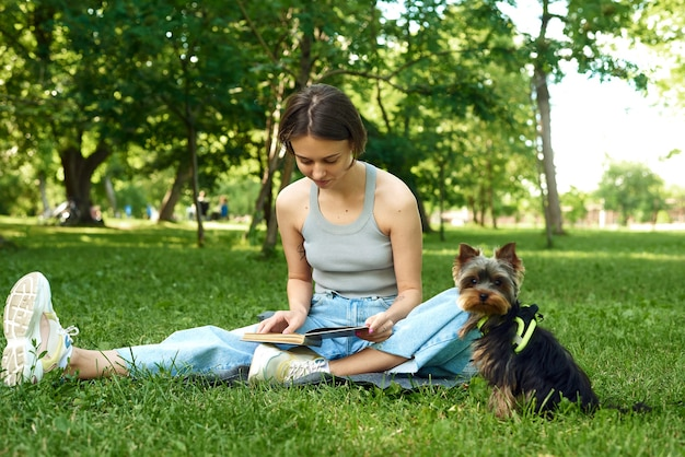 Eine junge frau liest ein buch in der natur neben ihrem kleinen hund yorshir terrier.