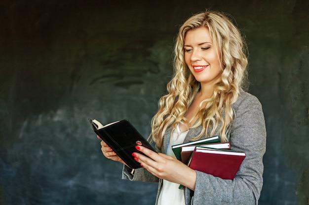 Eine junge frau liest und hält viele bücher.