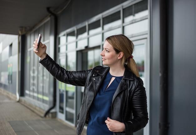 Eine junge frau macht ein foto von sich auf ihrem handy in der nähe eines einkaufszentrums