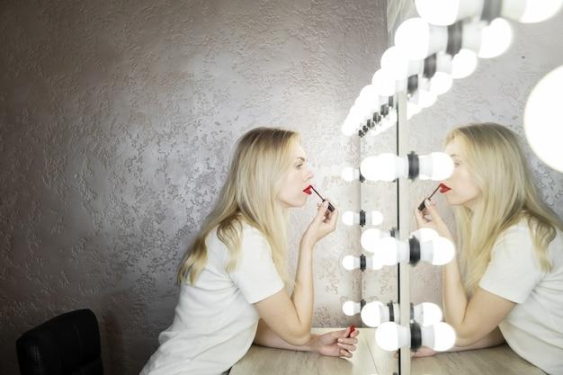 Eine junge frau macht helles make-up mit roten lippen vor einem spiegel in einem schönheitsstudio