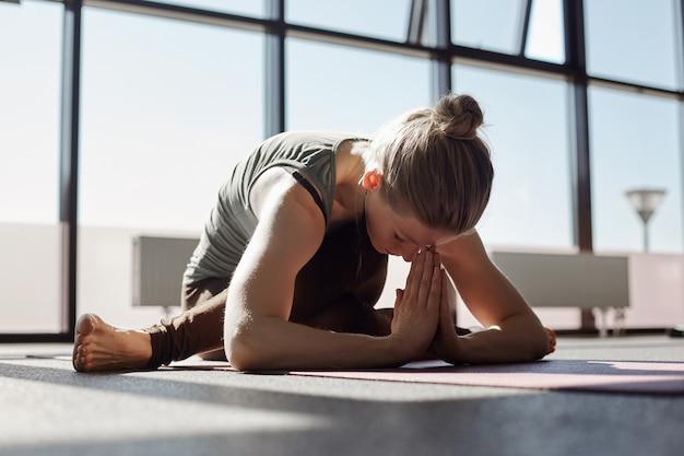 Eine junge frau macht yoga im fitnessstudio. ein mädchen meditiert vor dem hintergrund von panoramafenstern in einem modernen yoga-studio. typ, ort für text