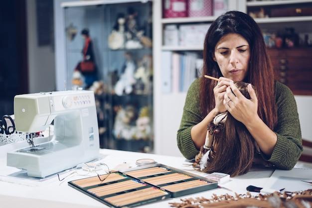 Eine junge frau malt das gesicht ihrer stoffpuppe