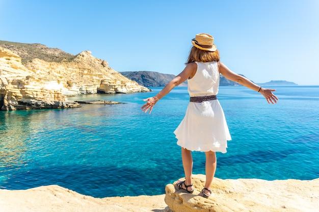 Eine junge frau mit blick auf das meer in rodalquilar in cabo de gata an einem schönen sommertag, almería