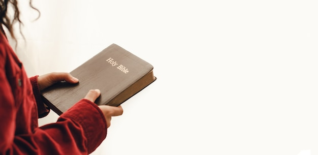 Eine junge frau mit der bibel auf weißem hintergrund nahaufnahme