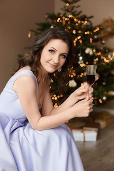Eine junge frau mit einem glas wein in ihrer hand, die im innenraum mit weihnachtsbaum aufwirft