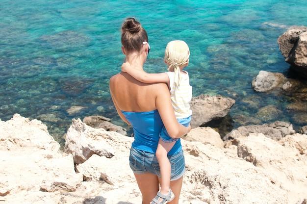 Eine junge frau mit einem kind schaut auf das meer, das mittelmeer, zypern