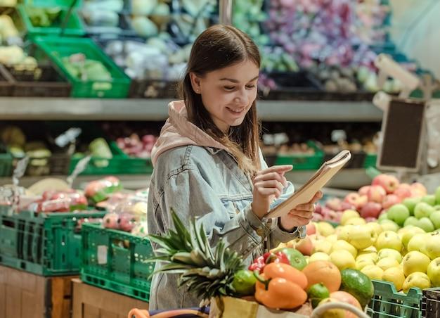 Eine junge frau mit einem notizbuch kauft lebensmittel im supermarkt