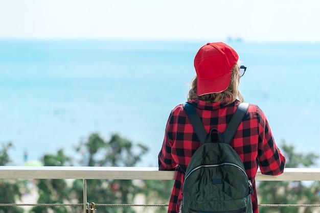 Eine junge frau mit einem rucksack steht auf einer gehbrücke und schaut auf das meer