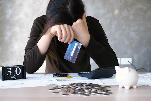 Eine junge frau mit einer kreditkartenschuld und vielen rechnungen auf den tisch gelegt.