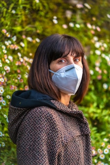Eine junge frau mit einer maske bei ihren ersten spaziergängen in misstrauen. erste spaziergänge der unkontrollierten covid-19-pandemie