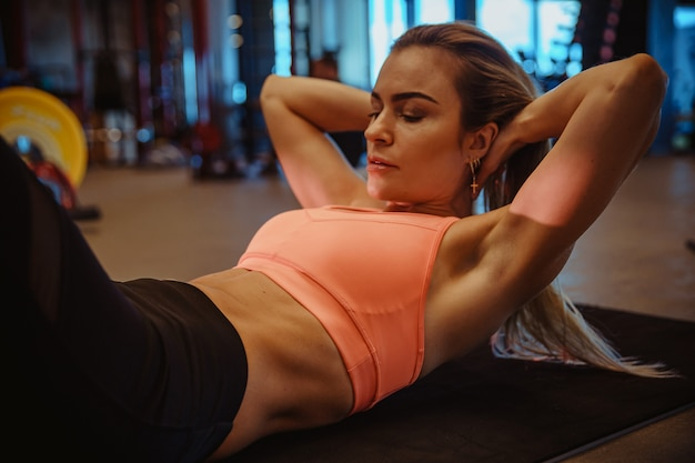 Eine junge frau mit einer sportfigur, die im fitnessstudio, in der fitness und im bodybuilding übt