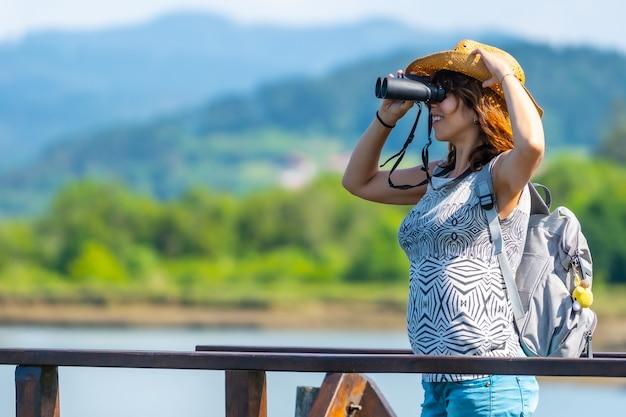 Eine junge frau mit fernglas betrachtet die vögel von den holzstegen des urdaibai-sumpfes, einem biosphärenreservat in bizkaia neben mundaka. baskenland