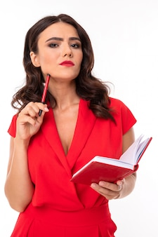 Eine junge frau mit hellem make-up in einem roten sommerkleid steht mit einem notizbuch und denkt an ihre notizen