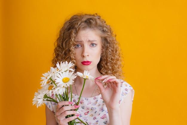 Eine junge frau mit lockigem blondem haar, die einen strauß gänseblümchen hält