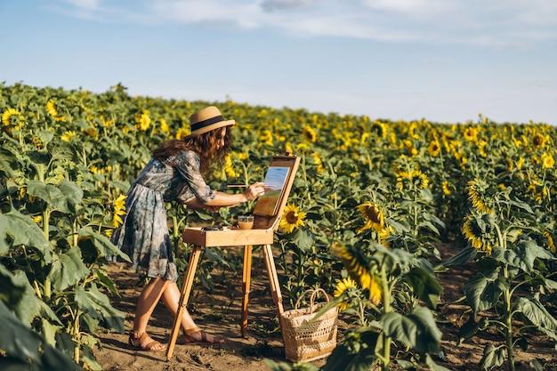 Eine junge frau mit lockigem haar und hut malt in der natur. eine frau steht in einem sonnenblumenfeld an einem schönen tag