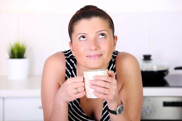 Eine junge frau mit morgenkaffee in der küche