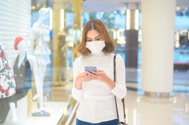 Eine junge frau mit schutzmaske im einkaufszentrum, die nach dem covid-19-pandemiekonzept einkauft.