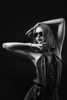 Eine junge frau mit schwarzem overall und schwarzer brille hält ihre hände in form eines rahmens in der nähe ihres kopfes und wirft auf. modefotografie im schwarz-weiß-stil.