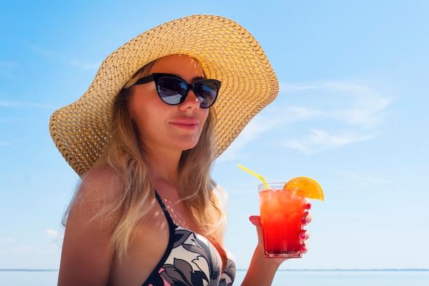 Eine junge frau mit sonnenbrille und strohhut hält einen cocktail in der hand gegen den blauen himmel und das meer. glücksmädchen tragen bikini am strand im urlaub oder urlaub. entspannen und partykonzept.