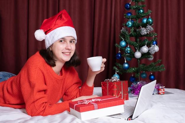 Eine junge frau mit weihnachtsmütze und rotem pullover hält eine tasse kaffee oder tee, ruht mit ihrem laptop auf dem bett, umgeben von weihnachtsgeschenken. online-shopping zu weihnachten