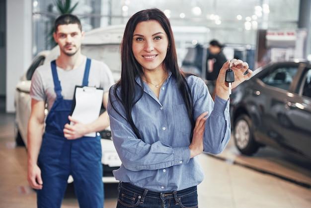 Eine junge frau nimmt ein auto vom autowerkstatt. sie ist glücklich, weil die arbeit perfekt gemacht ist