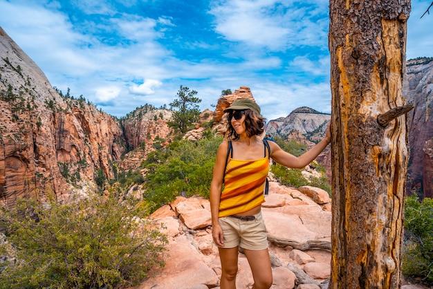 Eine junge frau oben auf dem trekking des angels landing trail im zion national park