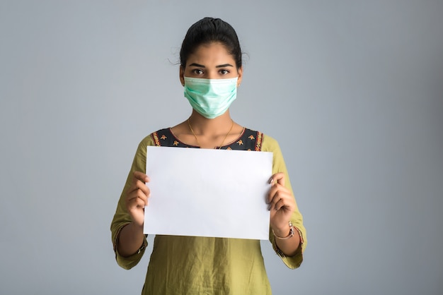 Eine junge frau oder ein junges mädchen in einer medizinischen maske, die ein brett der epidemie des coronavirus, covid-19 hält
