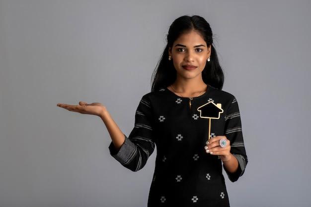 Eine junge frau oder geschäftsfrau, die ein kleines ausgeschnittenes brett in ihren händen an einer grauen wand hält.