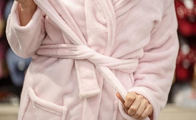 Eine junge frau probiert einen bademantel in einem geschäft an. nahansicht.