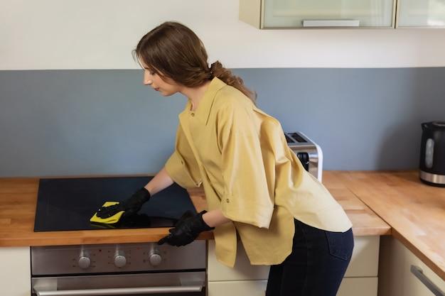 Eine junge frau räumt in der küche auf und spült geschirr. sie ist müde und nicht zufrieden mit der tatsache, dass sie es tun muss.